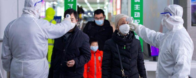Två personer tar temperaturen på resan kineser