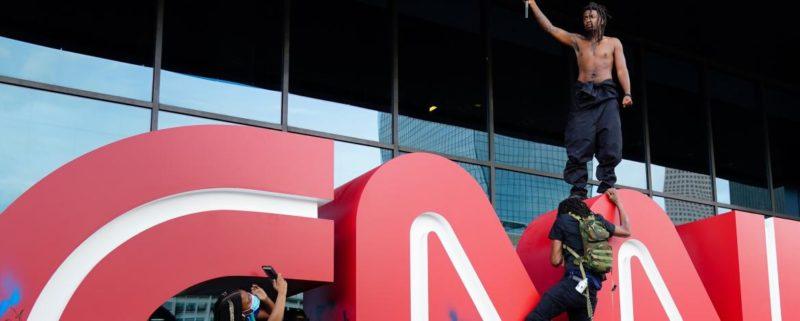 En man viftar med en flagga med texten Black Lives Matter. Han står på en CNN-skylt. Bilden är från protesterna mot polisen som dödade George Floyd utanför CNN den 29 maj, 2020