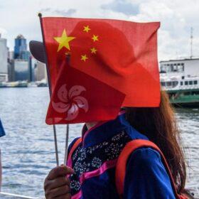 Dam med kinesisk flagga framför ansiktet i Hongkong