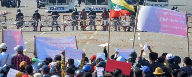 Pro-democracy demonstrators face riot police on an avenue in the capital, Naypyidaw, on 9 February (photo: STR / AFP).
